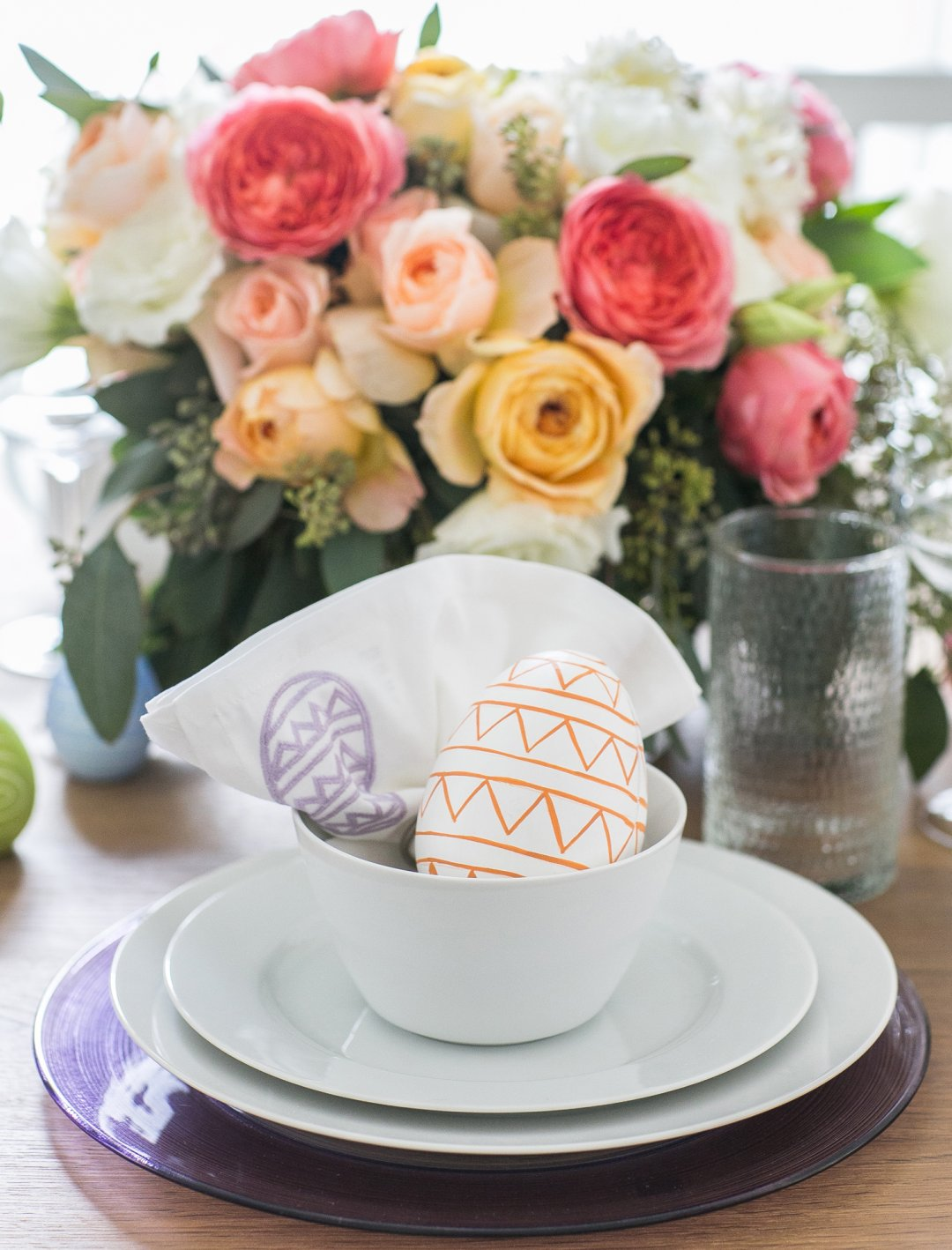 Orange Easter egg in white bowl at place setting