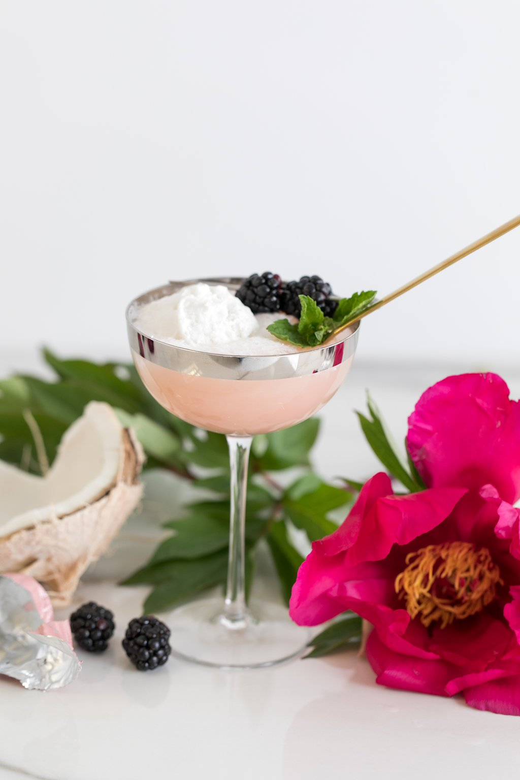 Coconut sorbet float in coupe glass with golden spoon next to pink peony and coconut shell