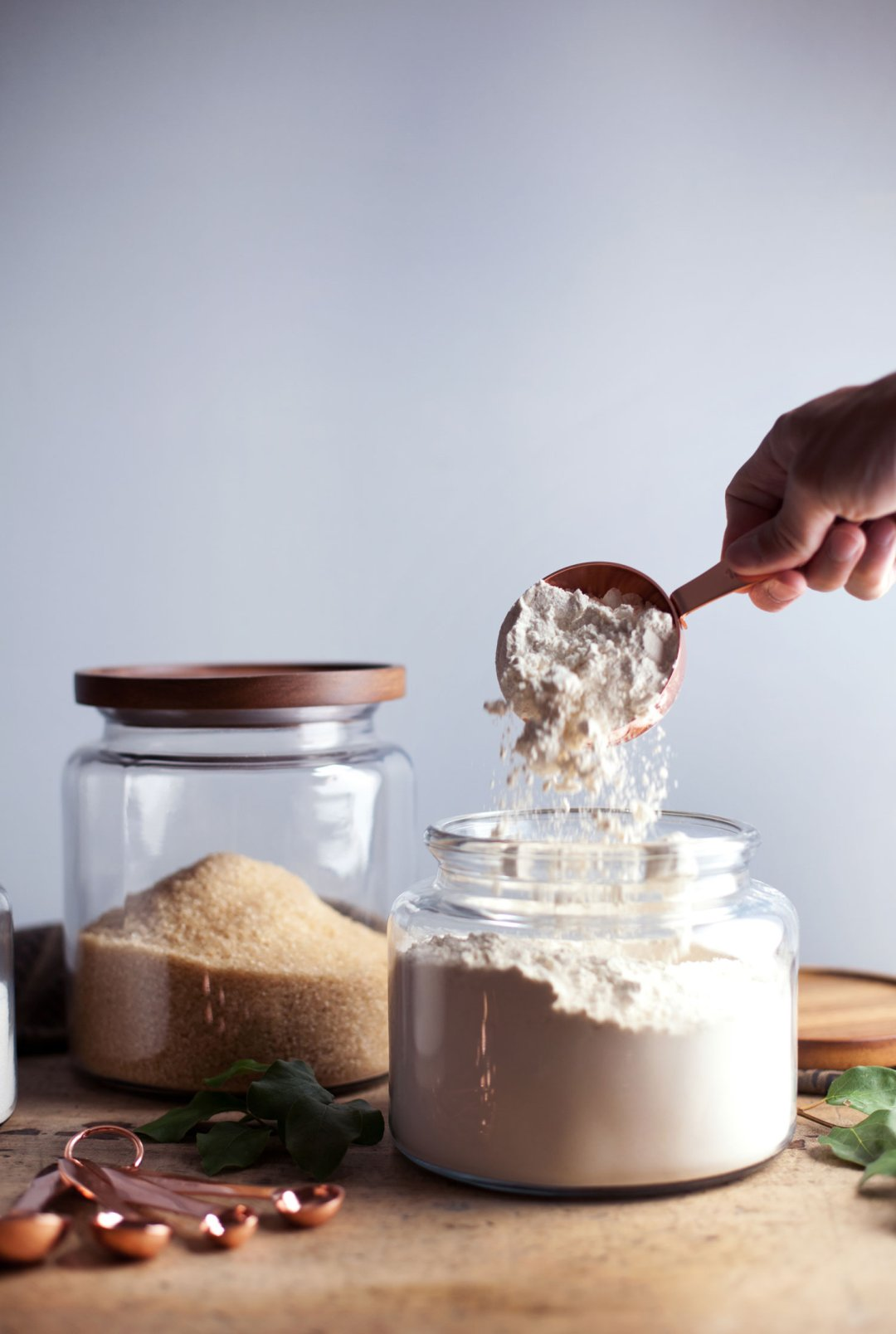 Scooping flour from a jar with a copper measuring cup