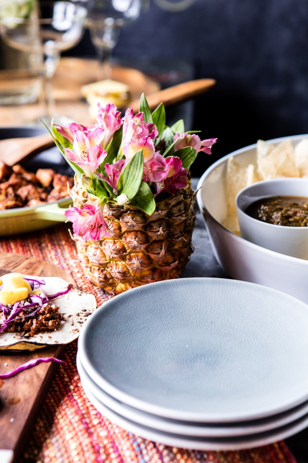 Stack of grey plates with pineapple and flowers in background and chips and dip to the right
