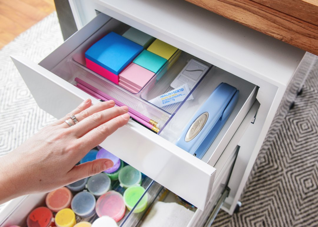 a supply cabinet containing painting supplies and office supplies