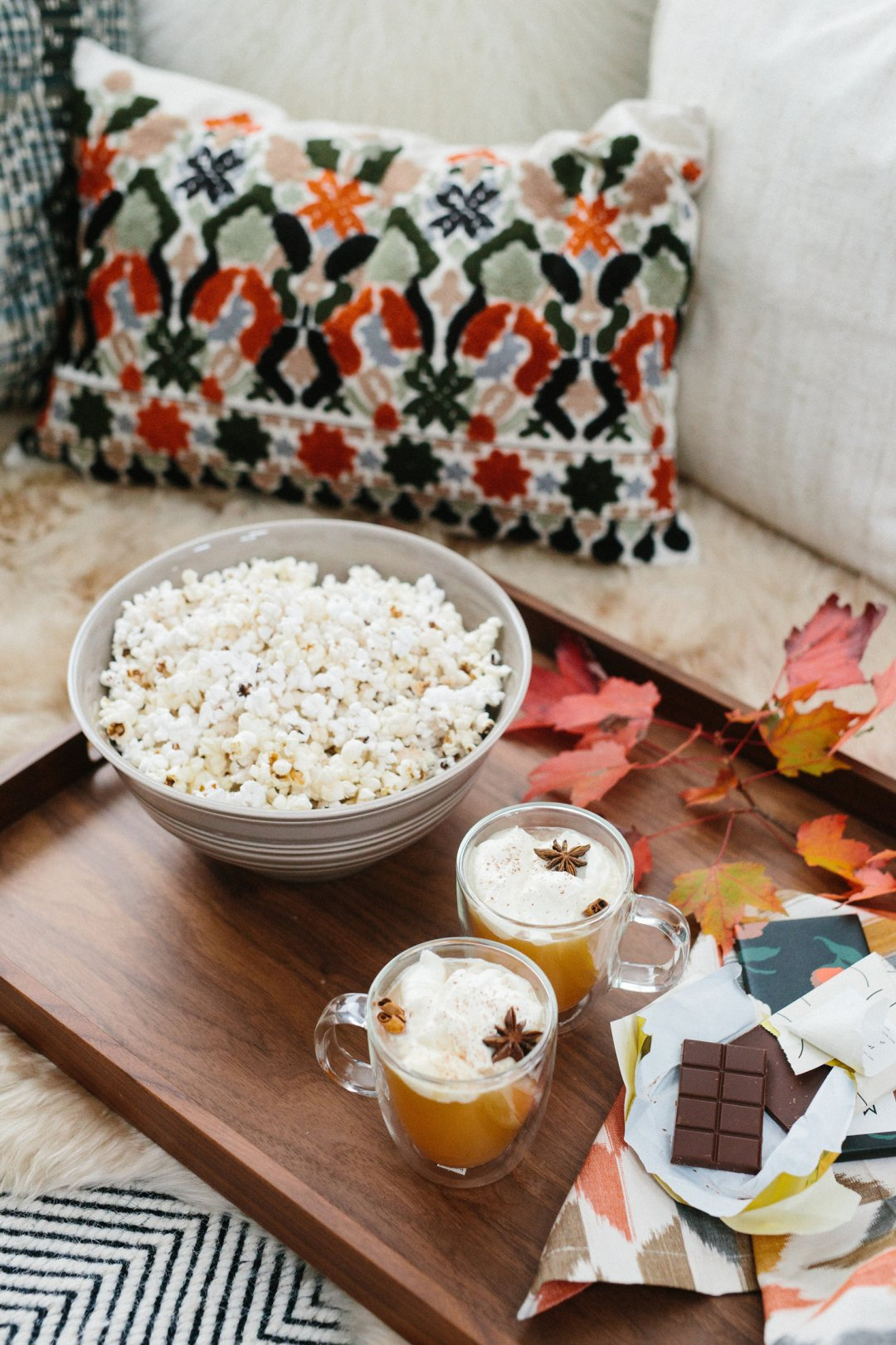 Popcorn, chocolate and orange cocktails on a wood serivng platter on a fur throw