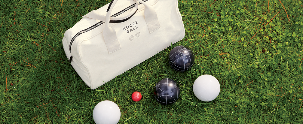 Bocce ball set and carrying case on grassy lawn