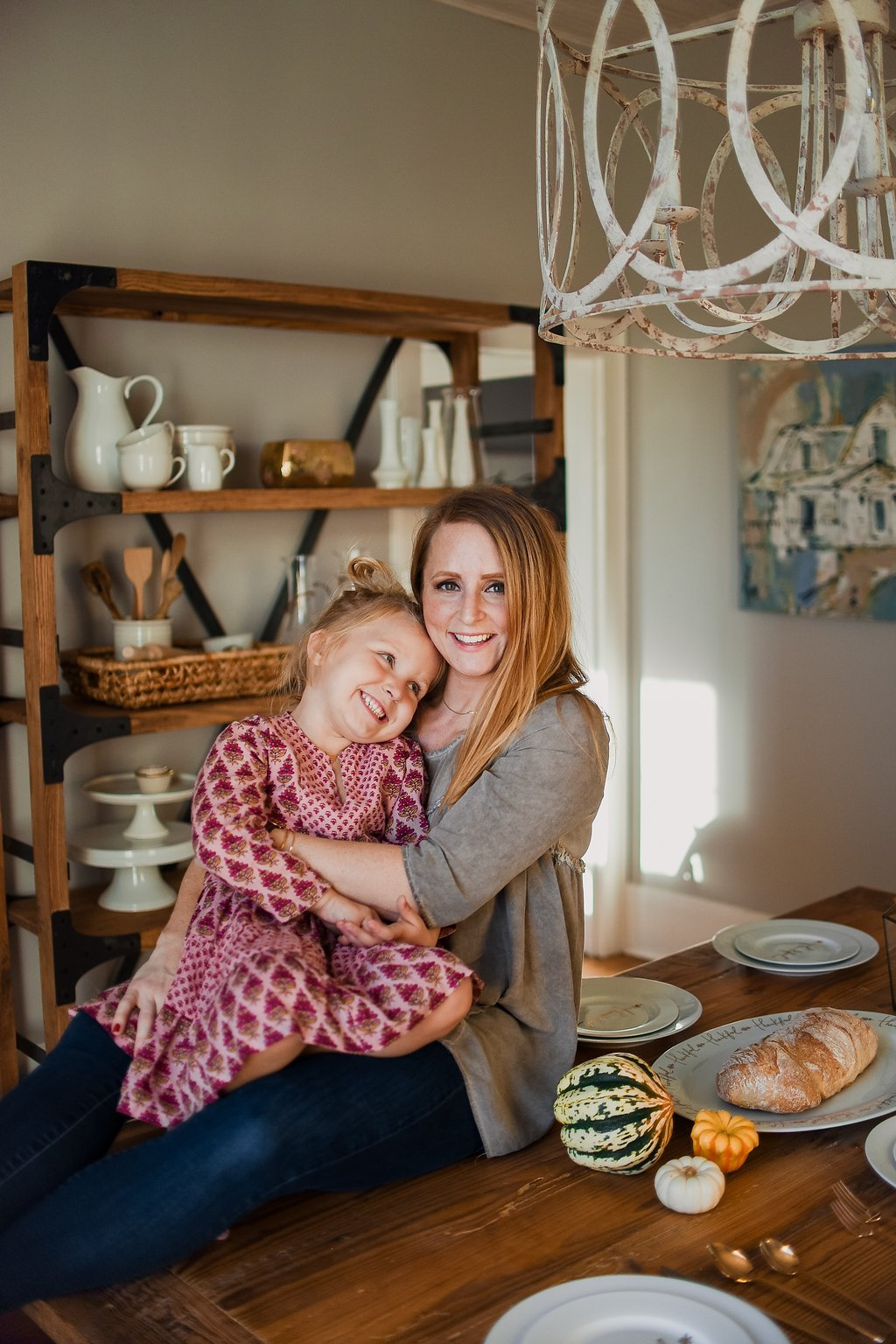 Mother and daughter hugging and sitting on a wood dining table set for Thanksgiving