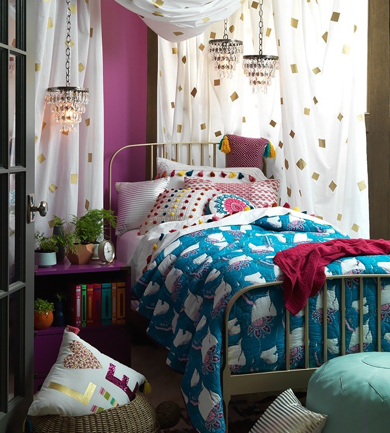 Curtains are hung around a bed to create a bohemian space.