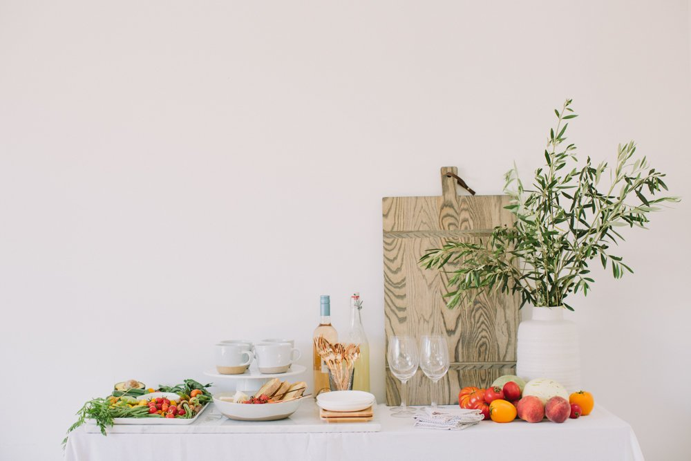 A white-clothed table with crudite, soup, bruschetta and wine arranged next to a fresh, green potted plan