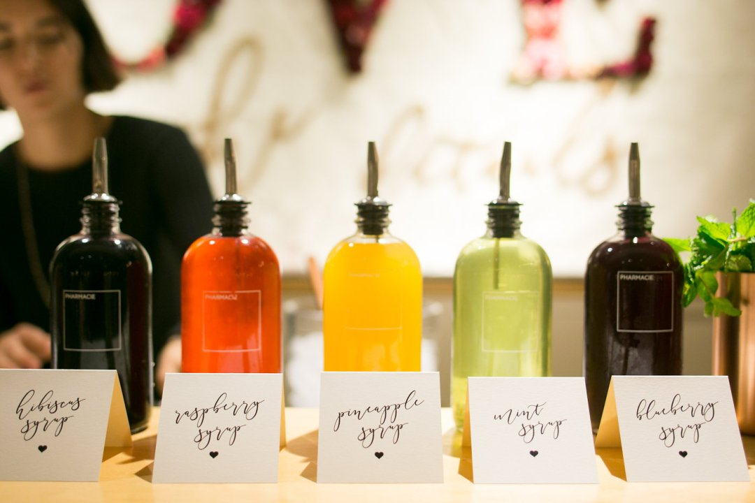 Colorful homemade cocktail syrups line the bar