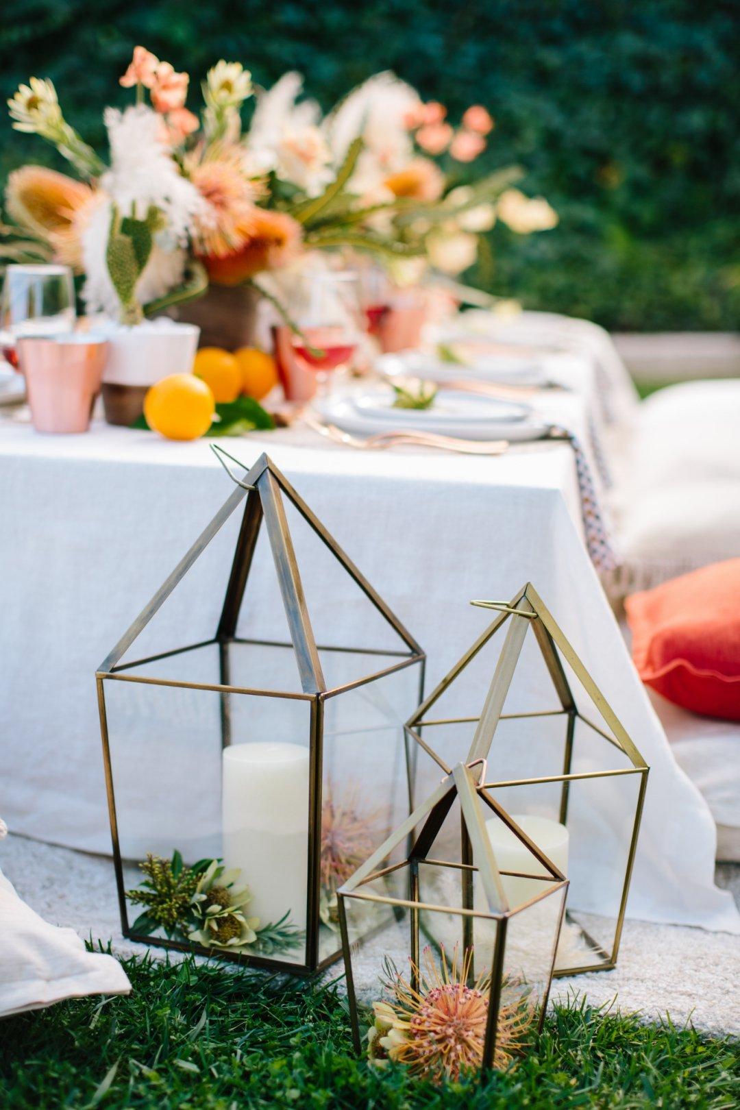 Brass lanterns in three sizes next to dinner table