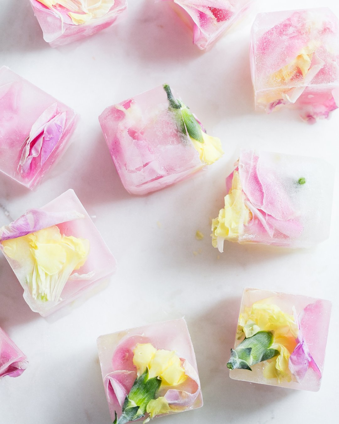 Pink flowers frozen into small ice cubes