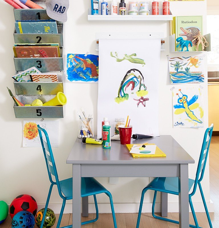 An art room has paintings on the wall and a craft table