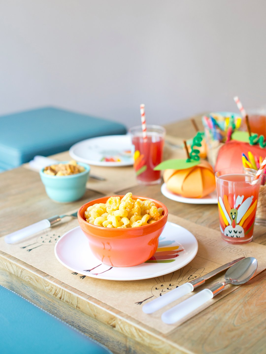 Kids Thanksgiving table place setting with a serving of mac and cheese in an orange bowl