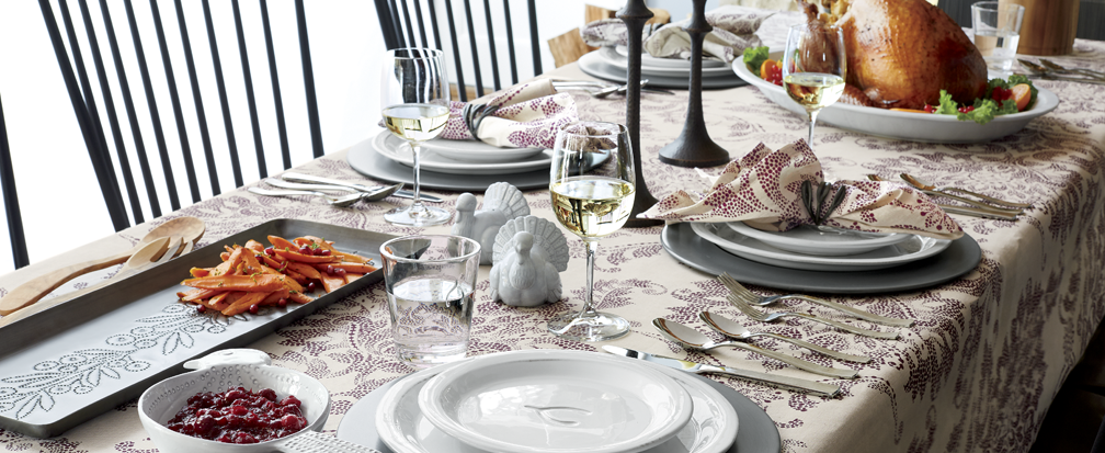 Thanksgiving dinner on a purple and white tablecloth with white dinnerware and wine