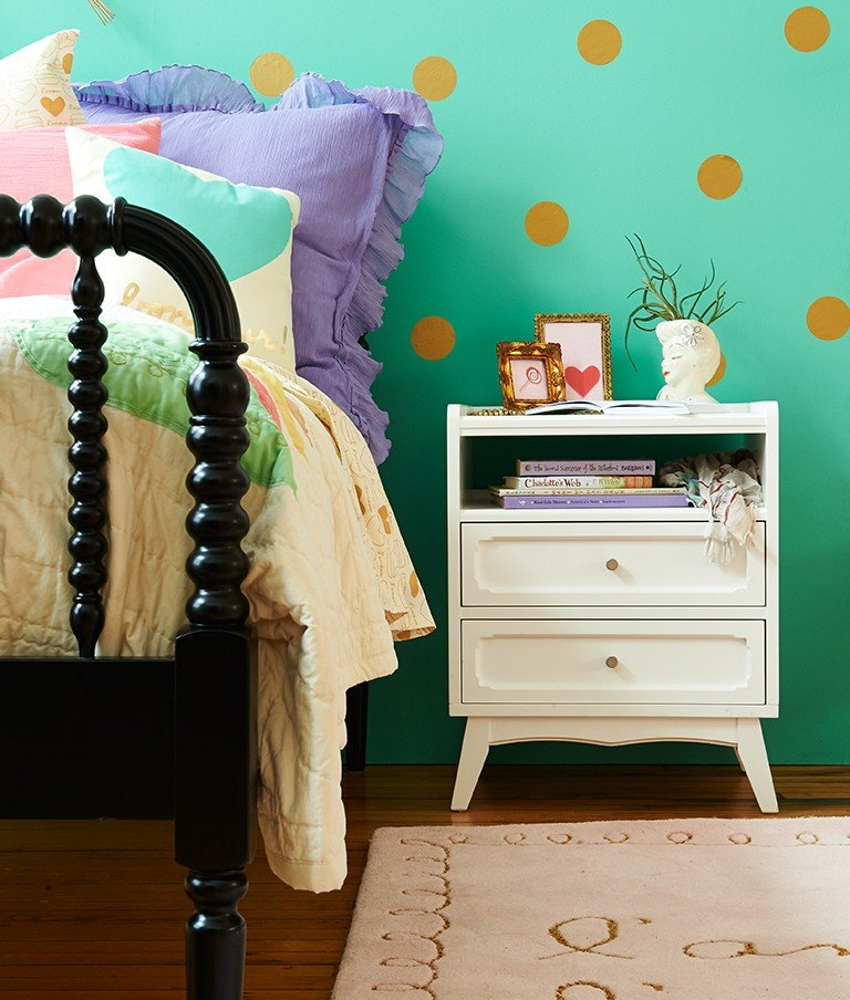 Gold wall decals create a polka dot wall in a girls room.