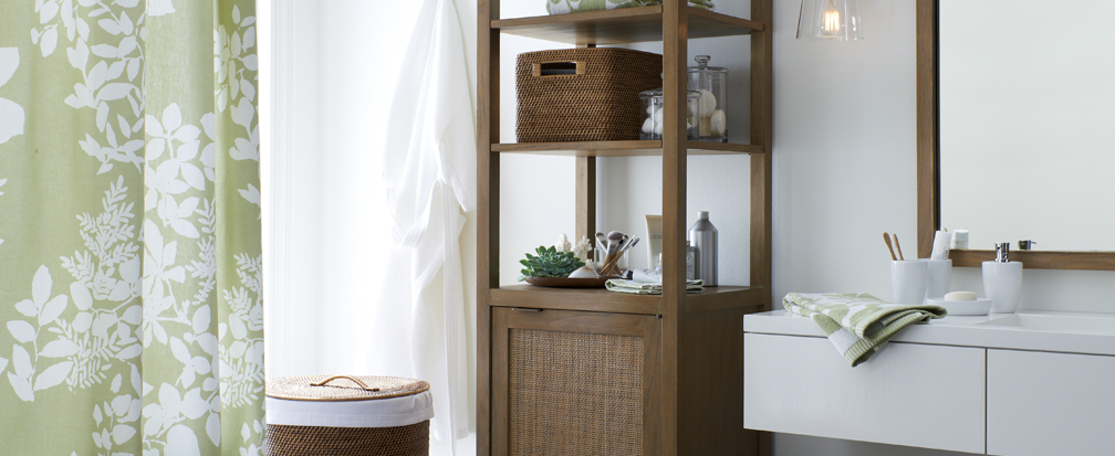 Green and white bathroom with brown wicker shelving and a wicker hamper