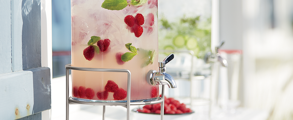Iced raspberry and mint drink in large glass cold drink dispenser with bowl of fruit and another drink dispenser in background