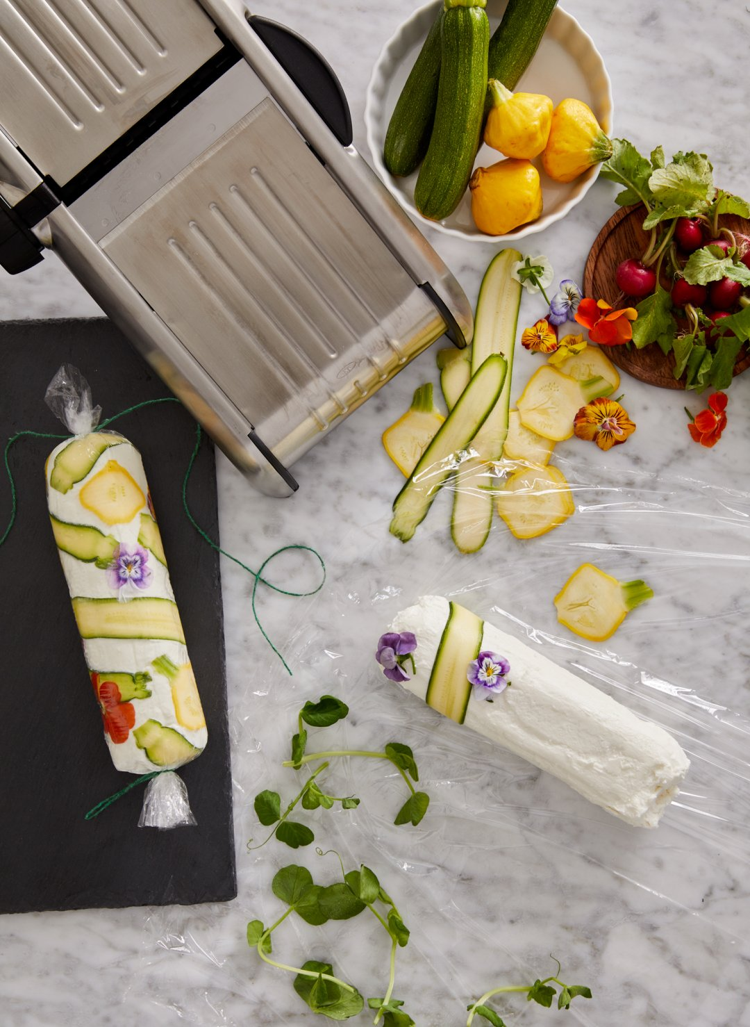 Slicing vegetables on a mandoline to make a goat cheese log