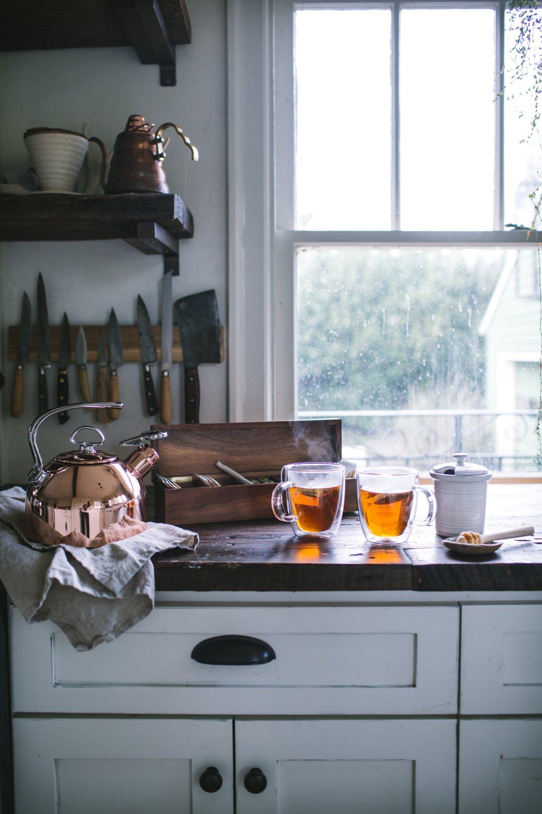Copper tea kettle, two mugs of steeping tea, honey pot, and tea box on countertop