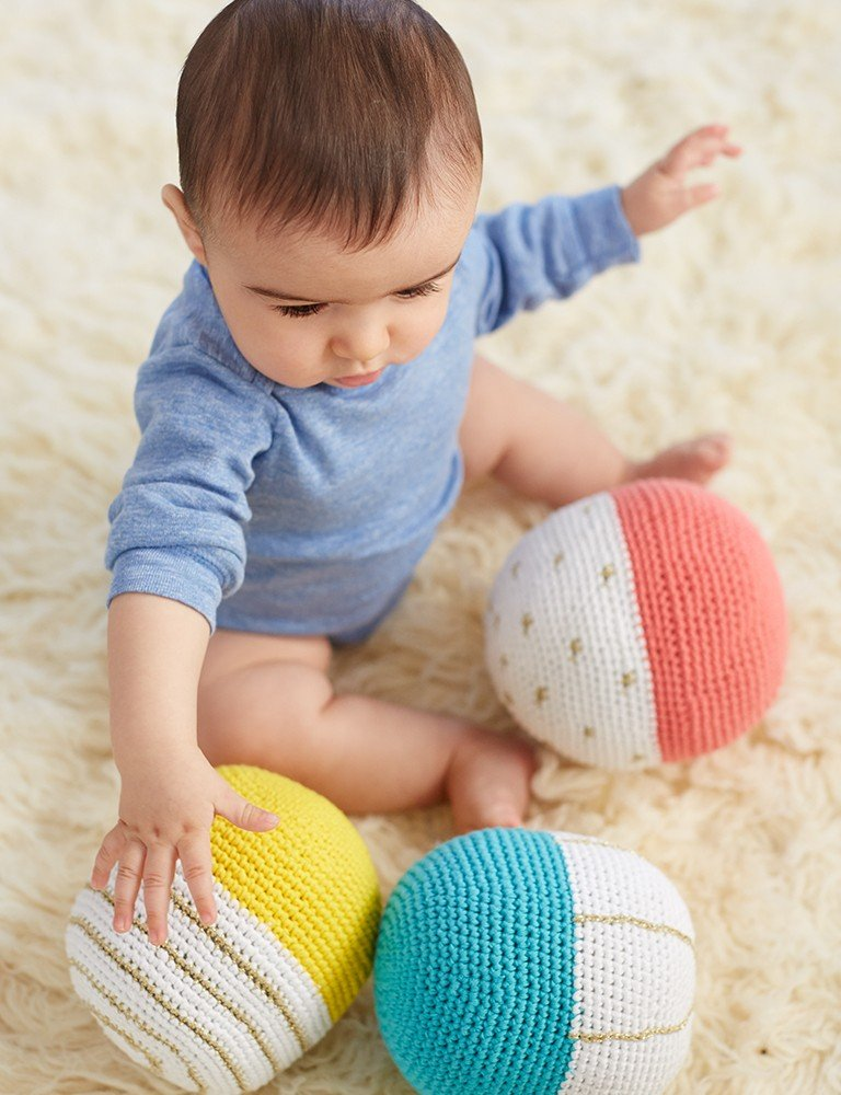 A baby plays with soft, knit balls.