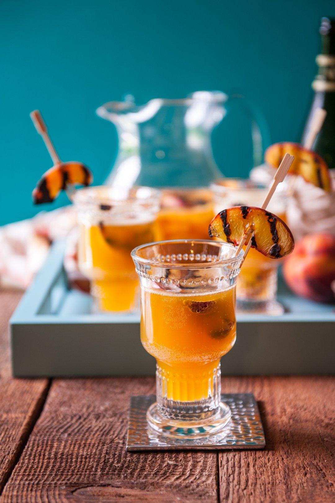 Peach sangria in serving glass on metal coaster on wood table