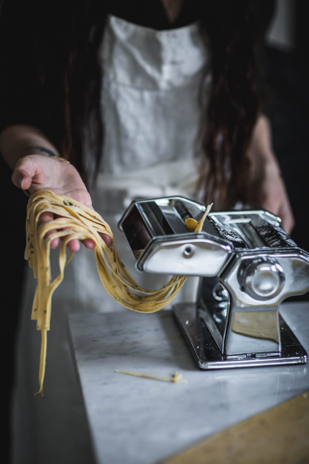 a woman catches fresh linguine coming out of a pasta maker