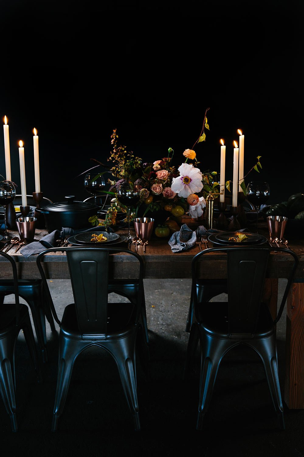 Dark wood dining table set for Thanksgiving with white taper candles, black place settings and centerpiece florals