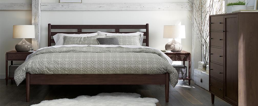 Dark wood bedroom furniture, grey comforter and sheepskin rug