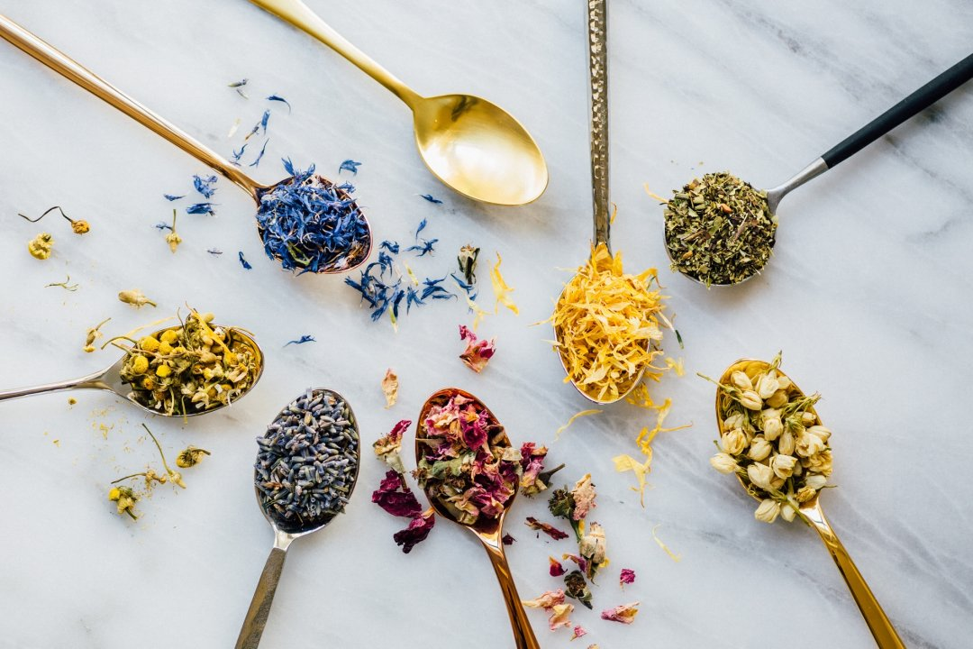 Eight spoons of different metal colors and shapes with various herbs for making tea