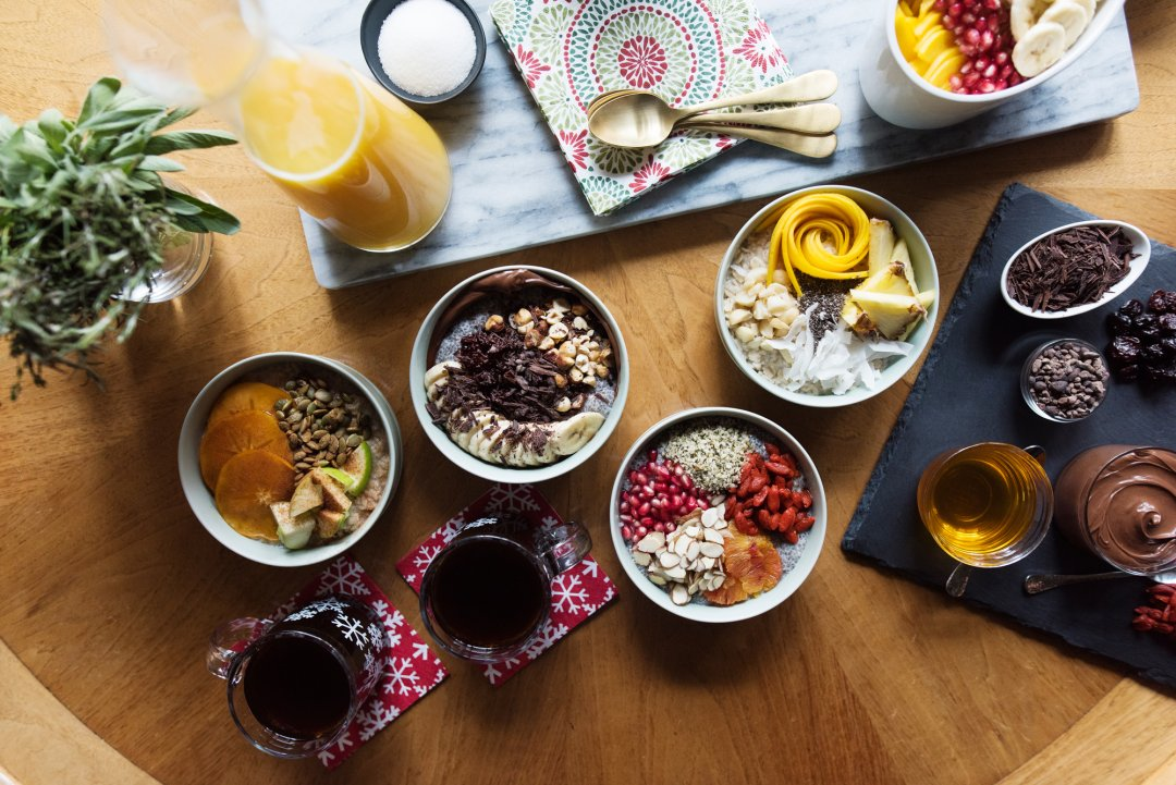 Four colorful smoothie bowls with various fruit and nut toppings laid out on a table with coffee and juice
