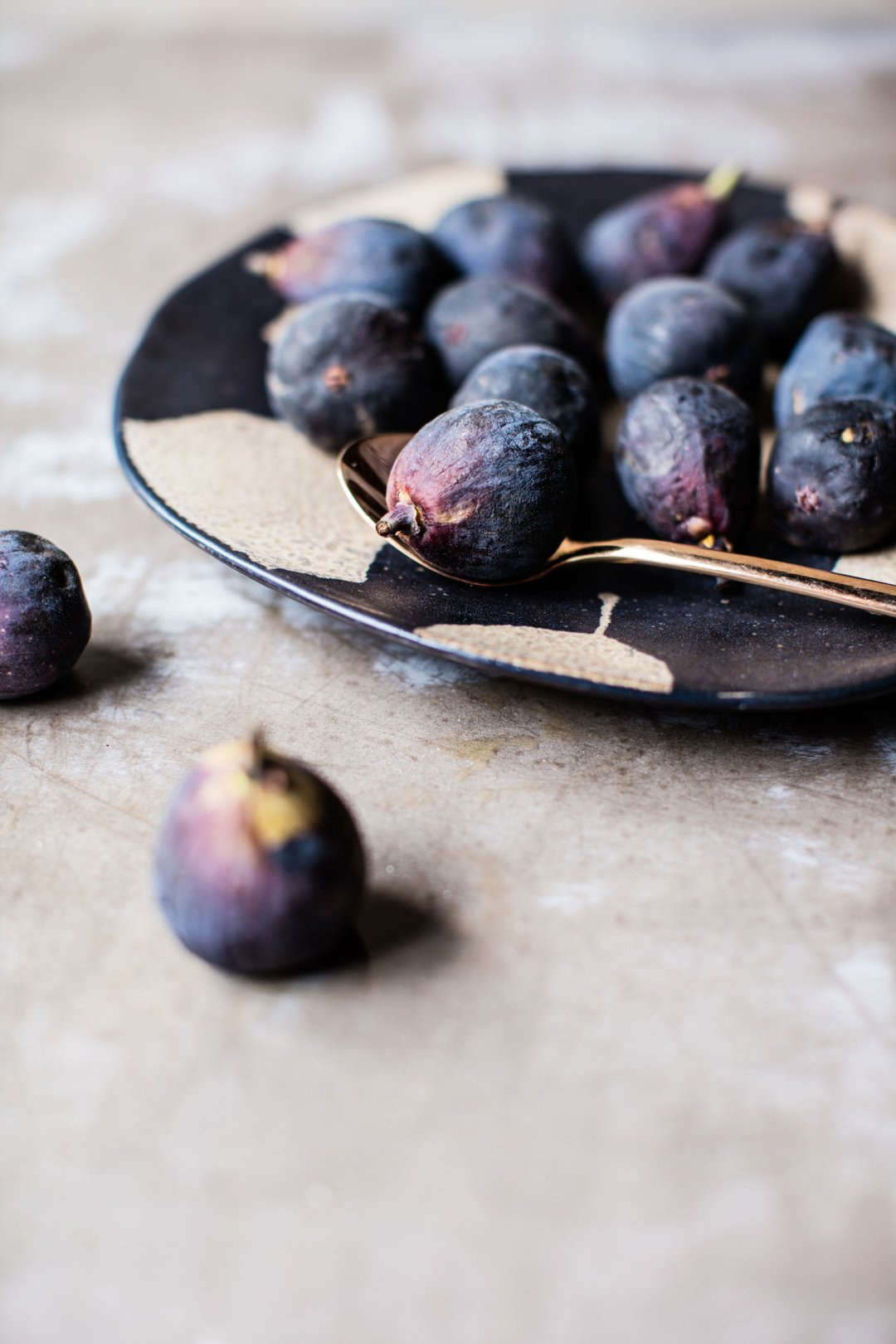 A platter of fresh black figs with a rose gold serving spoon