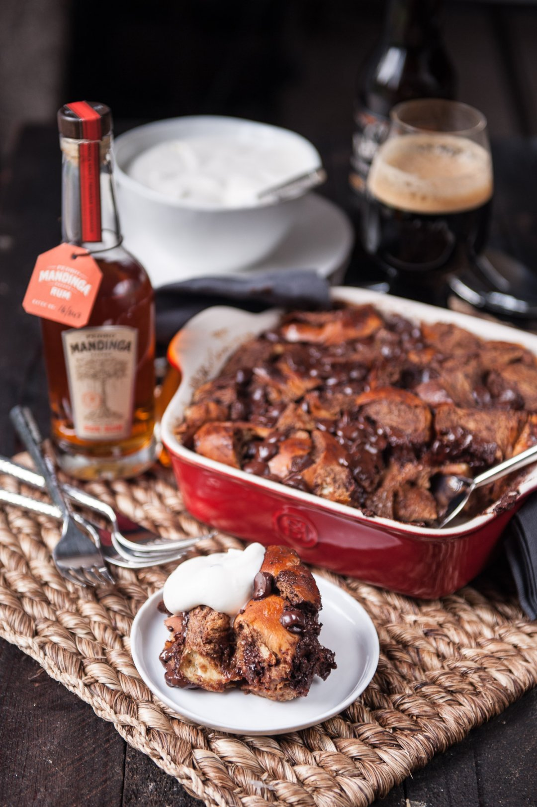 small plate of chocolate stout bread pudding surrounded by a bottle of rum a bowl of whipped cream a red dish of bread pudding and a glass of stout beer