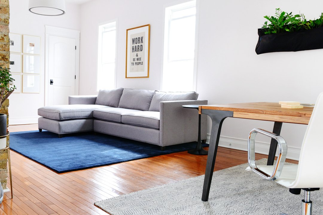 Studio living room with a grey sofa and chaise lounge on a midnight blue area rug