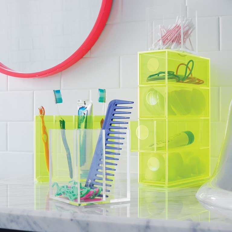 A bathroom counter is organized with actrylic bath accessories for toothpaste, toothbrushes and more.