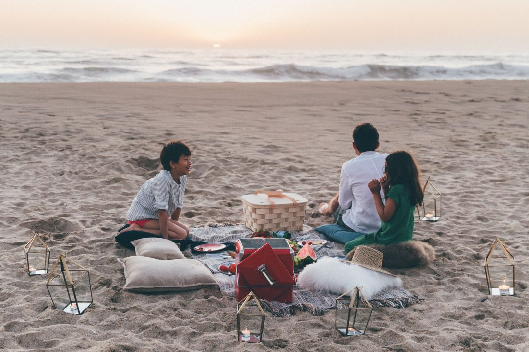 Lanterns surrounding family sitting on beach with picnic
