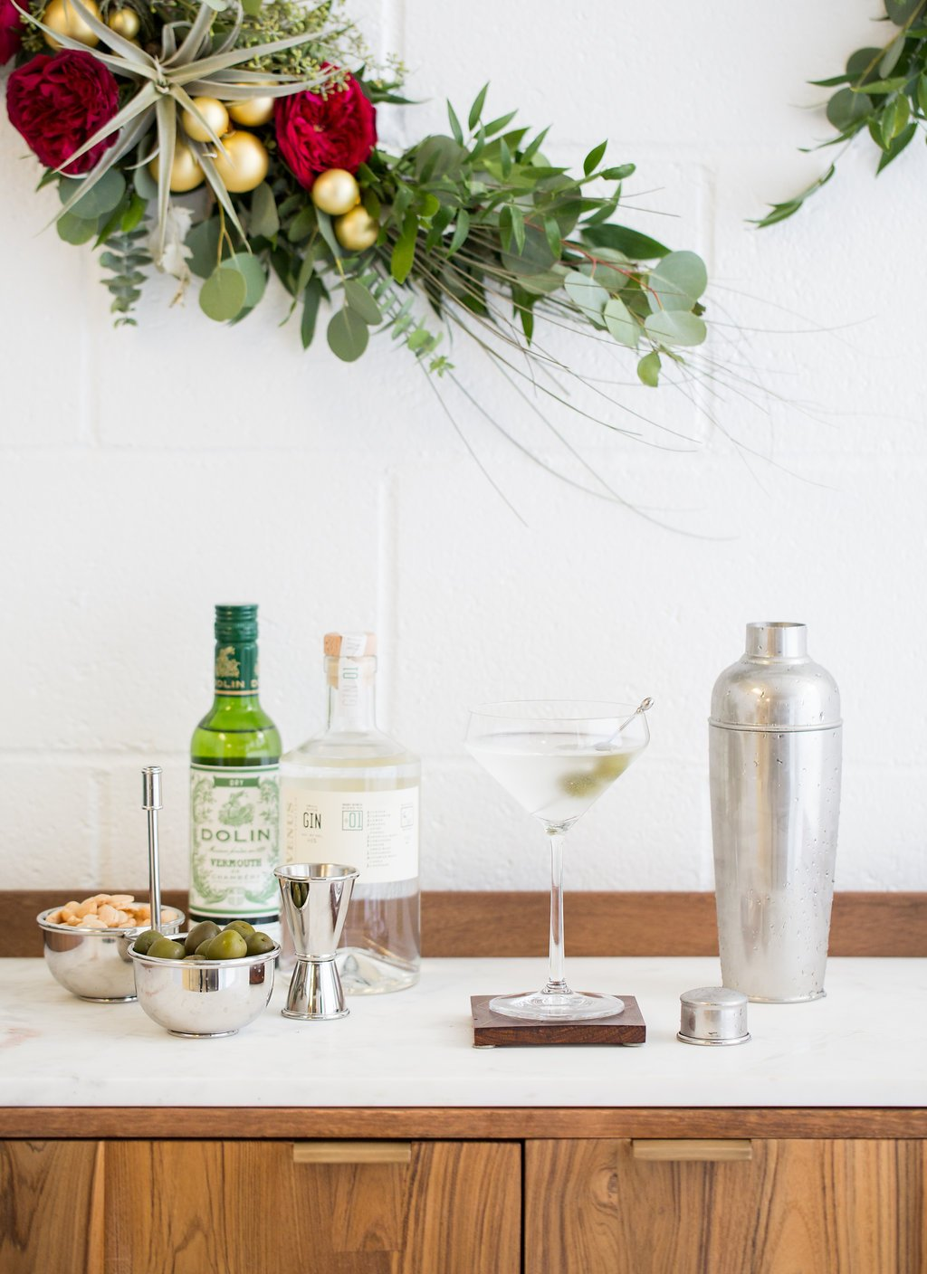 martini ingredients on top of a wooden cabinet beneath a wreath on a brick wall