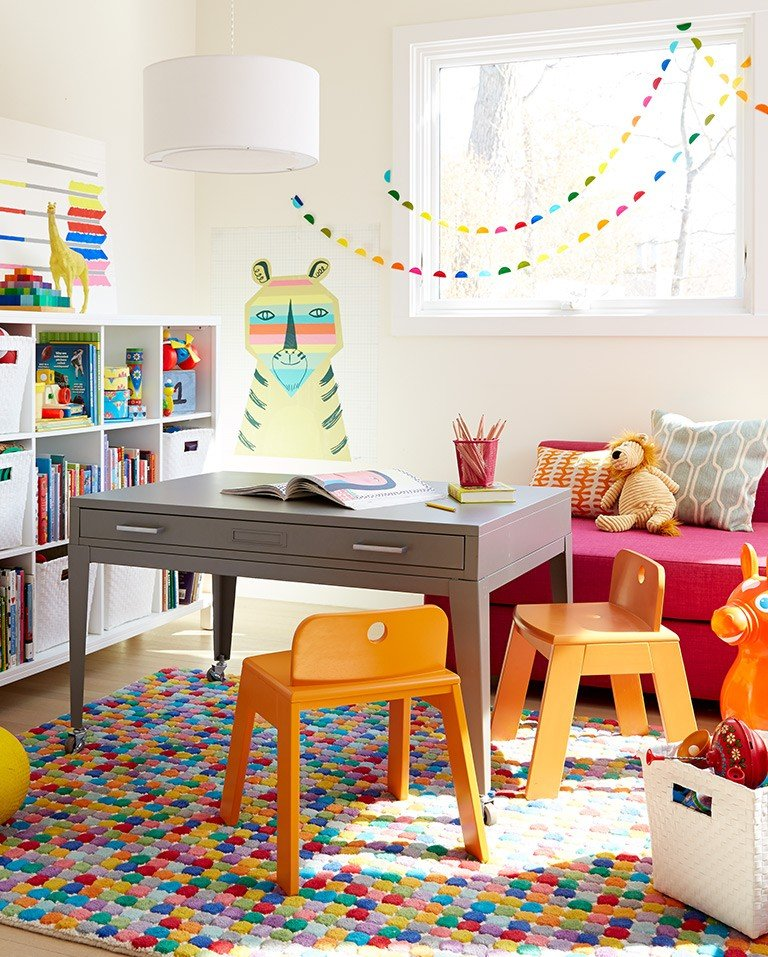 A desk doubles as an activity table in a colorful kids room.