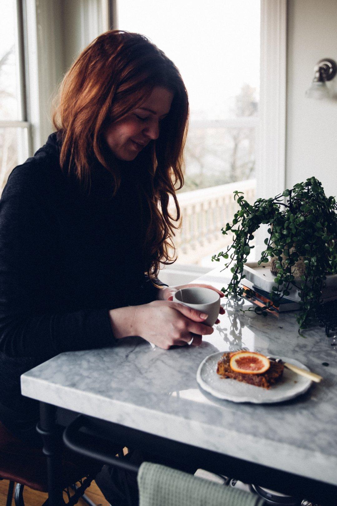 Christiann sitting at her kitchen island drinking tea