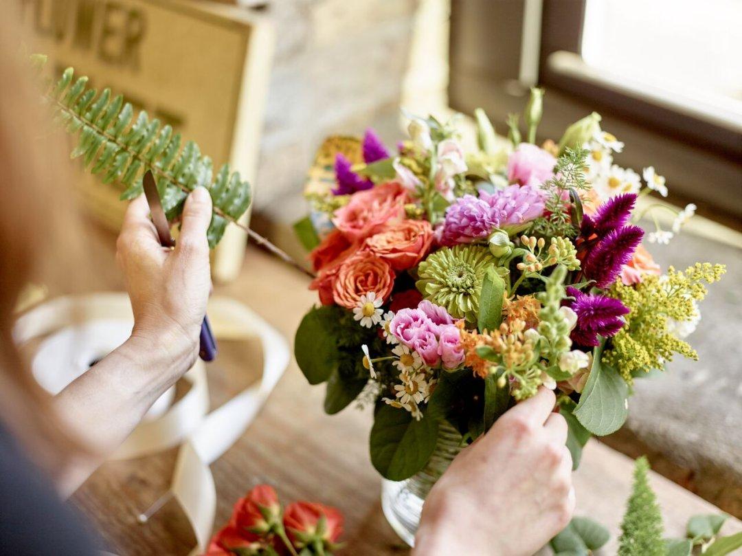 Florist putting leafy greenery into flower arrangement