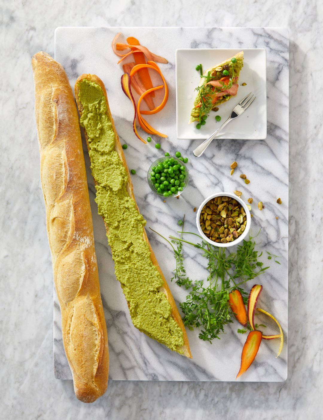 Pea and pistachio hummus spread on a baguette tartine on a marble board