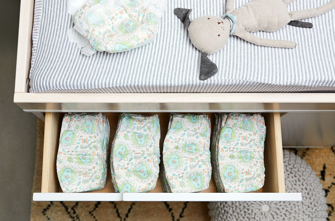 nursery changing table showing drawer of diapers
