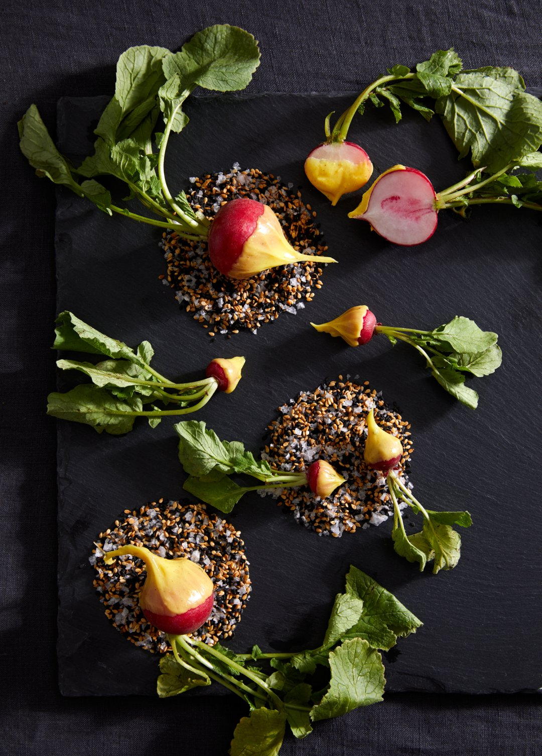 Radishes dipped in butter and salt on black slate cheese board