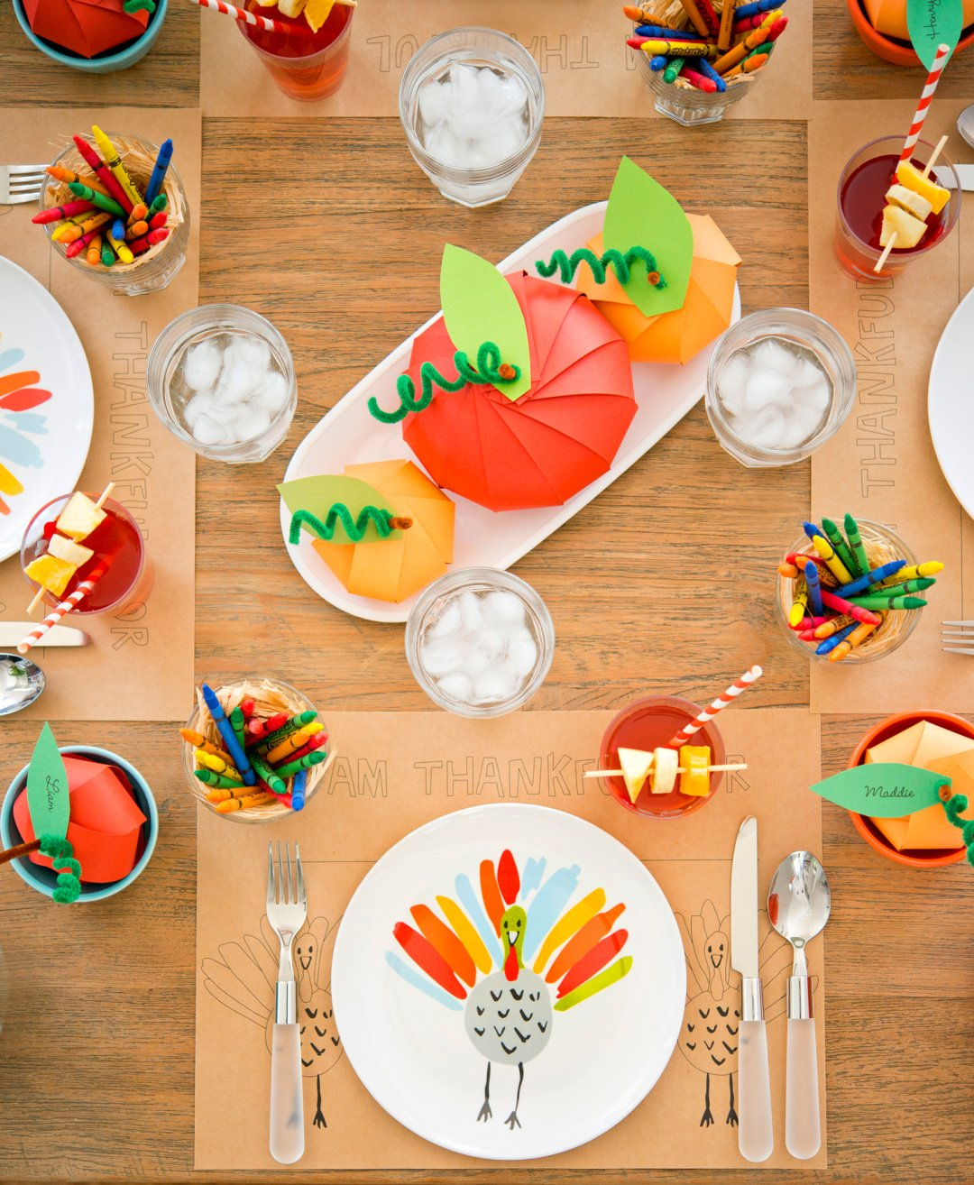 Homemade paper pumpkin centerpiece in white melamine serving dish on kids thanksgiving table