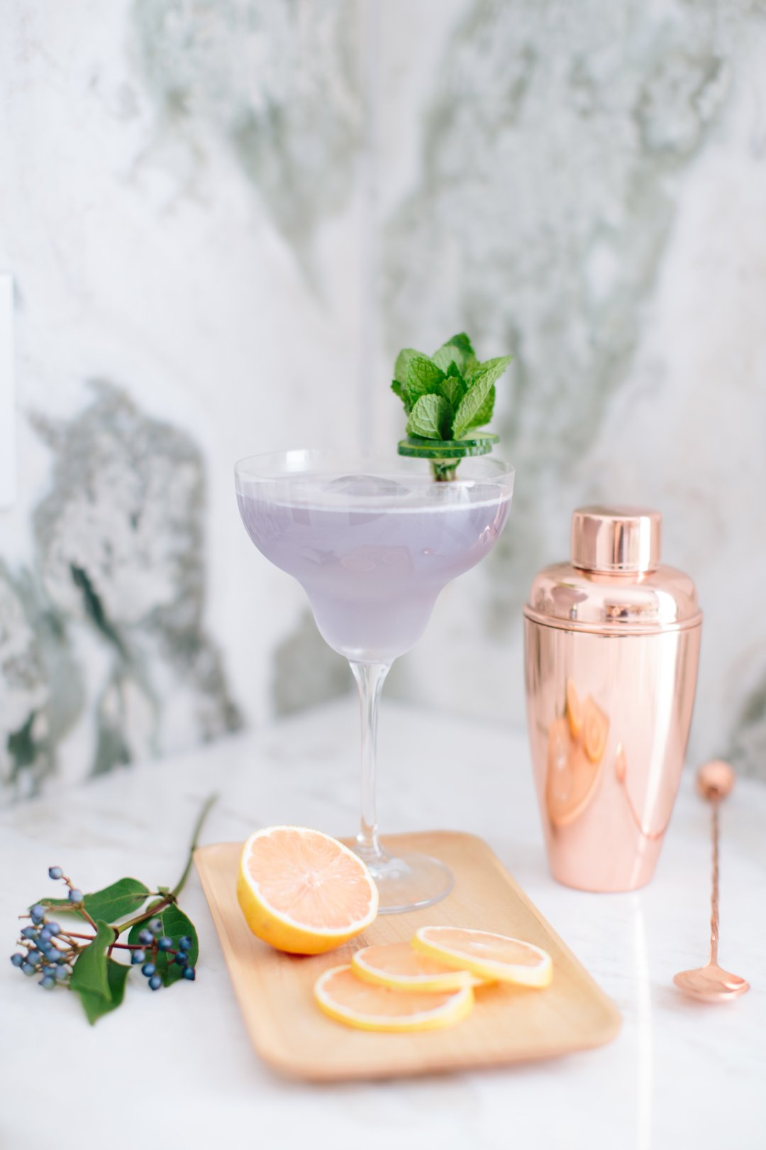 Violet Lemon Gin cocktail in a margarita glass with a copper cocktail shaker in the background