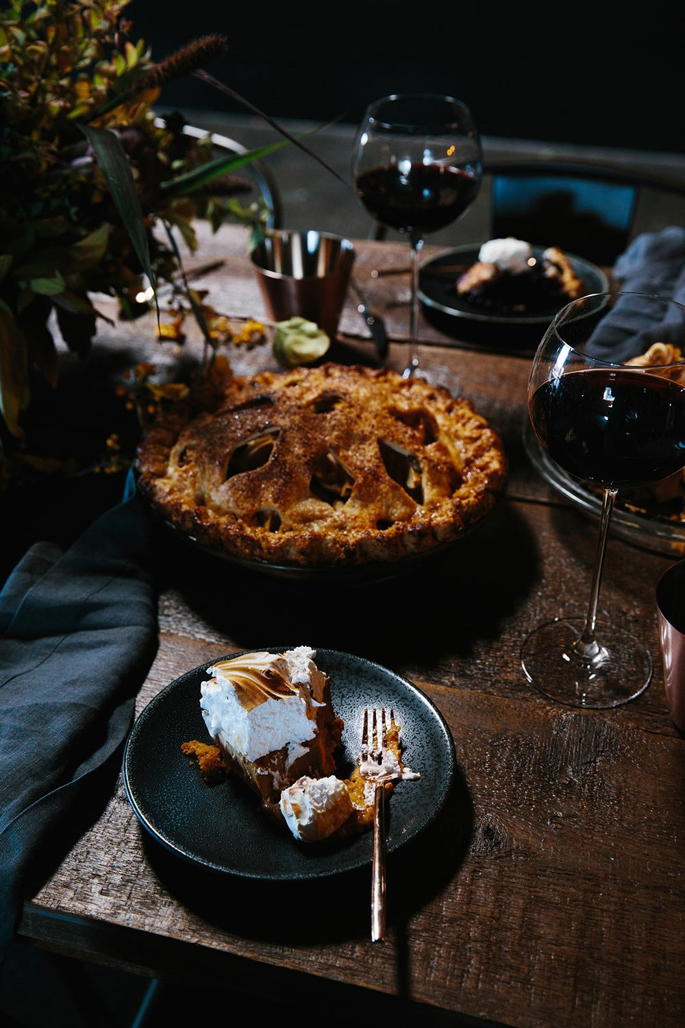 Slice of meringue pie on a black dinner plate next to a crispy holiday pie and a glass of red wine on a wood dining table