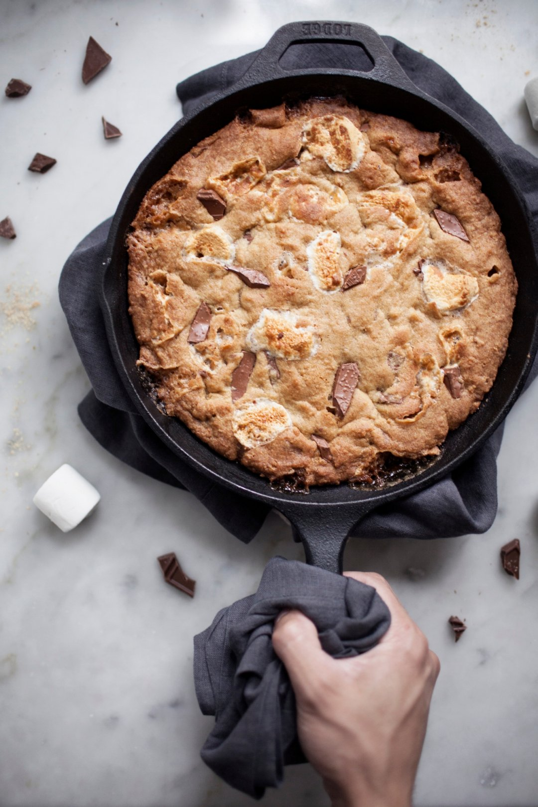 Hand holding skillet with cookie