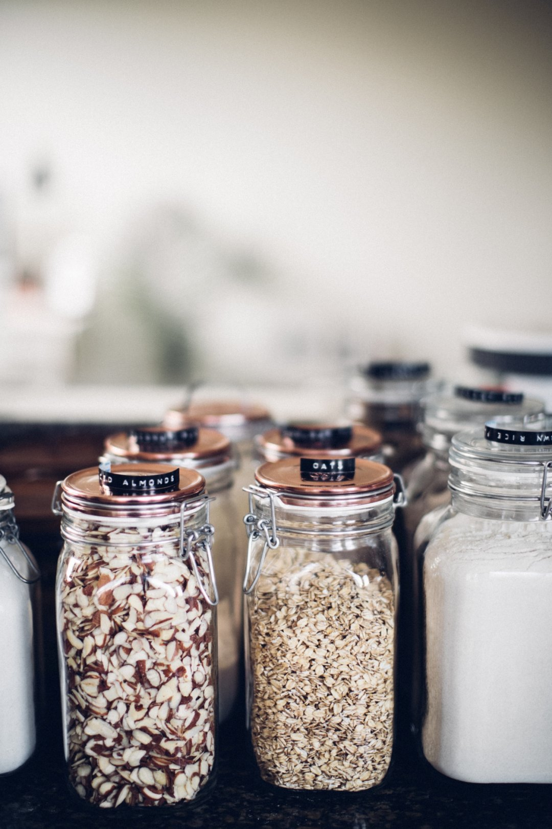 Nuts and other ingredients in glass jars with copper lids