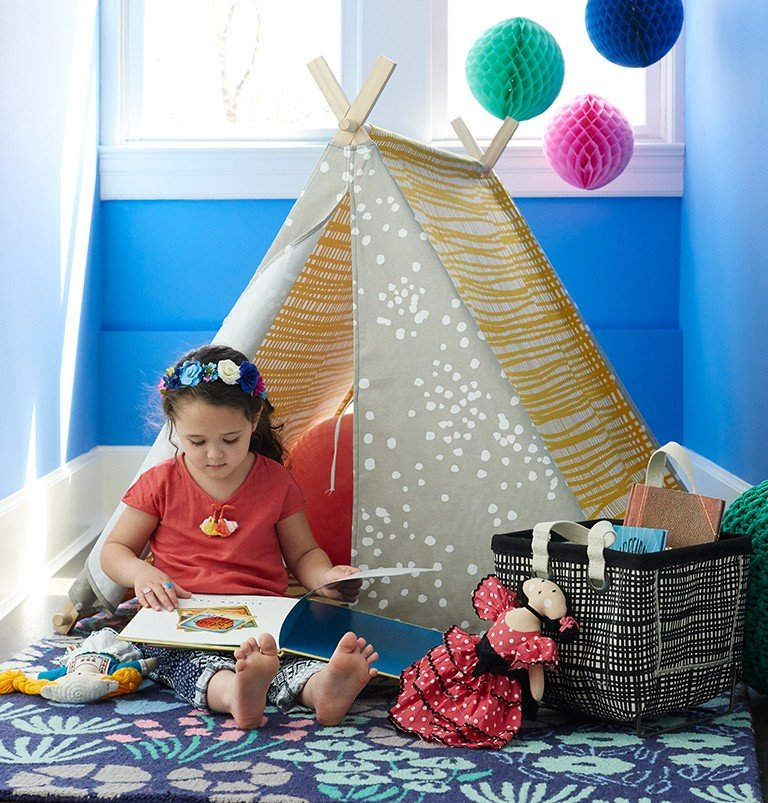 A play tent and basket of books create a reading book in a playroom