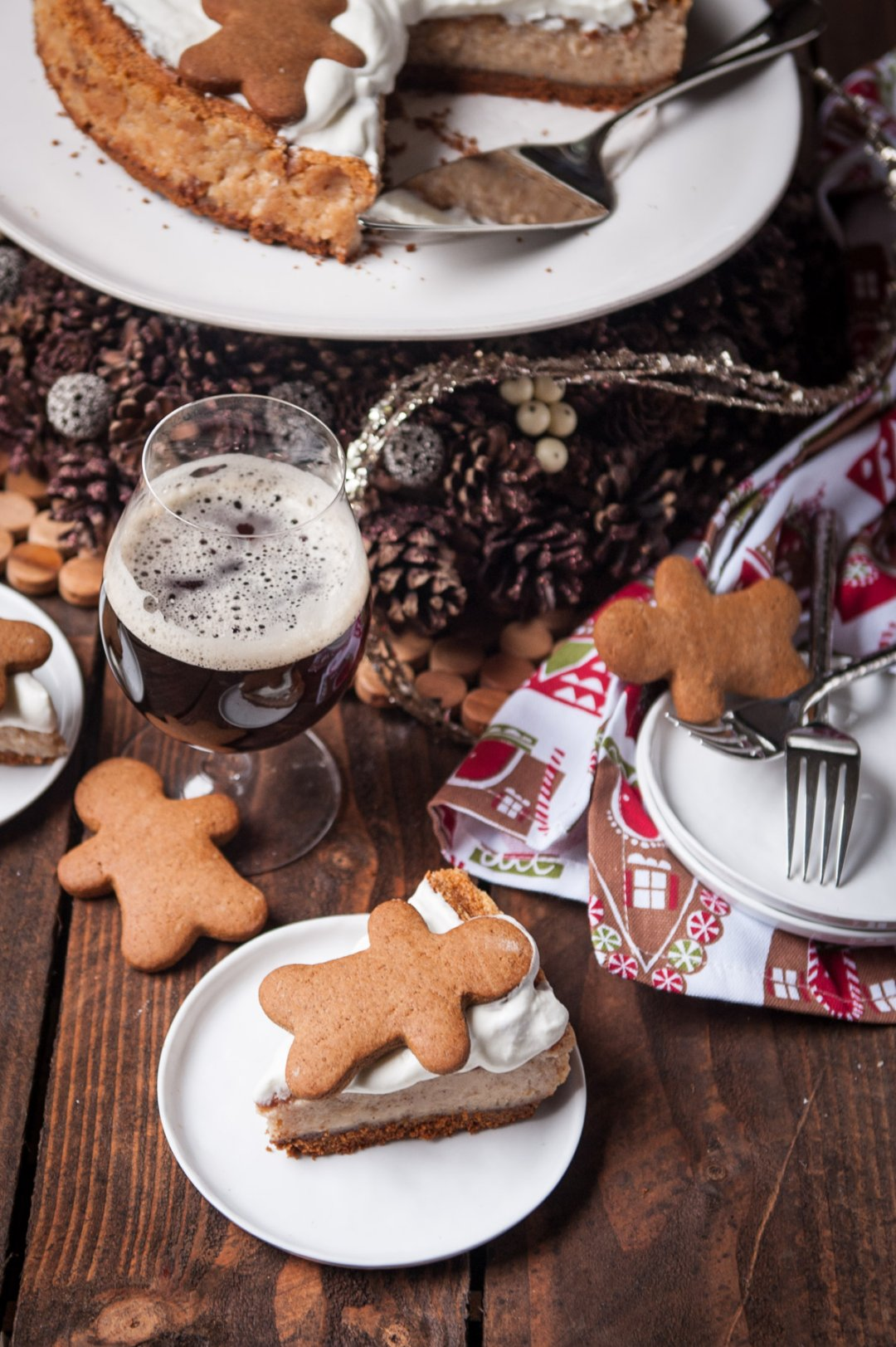 Cheesecake slice with a gingerbread man cookie on top on a small white plate next to a glass of dark beer
