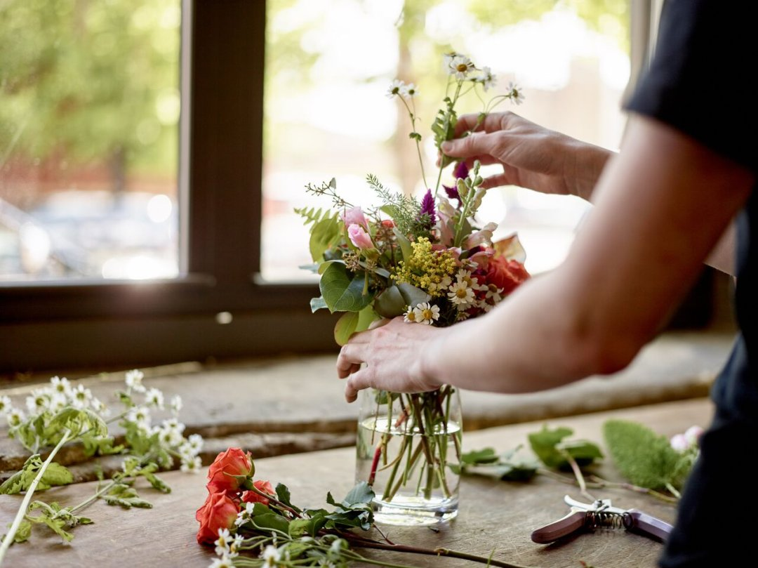Arranging flowers in a glass vase on a counter next to window