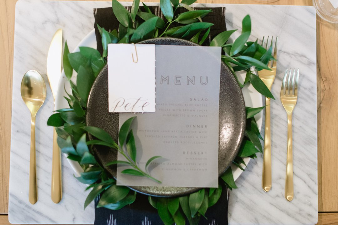 Black plate with greenery at wedding placesetting