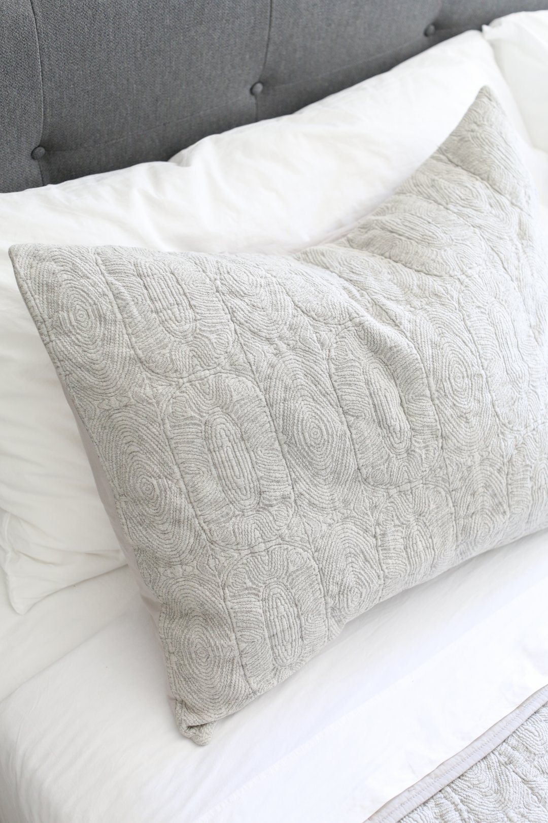 Pillow in grey sham on bed